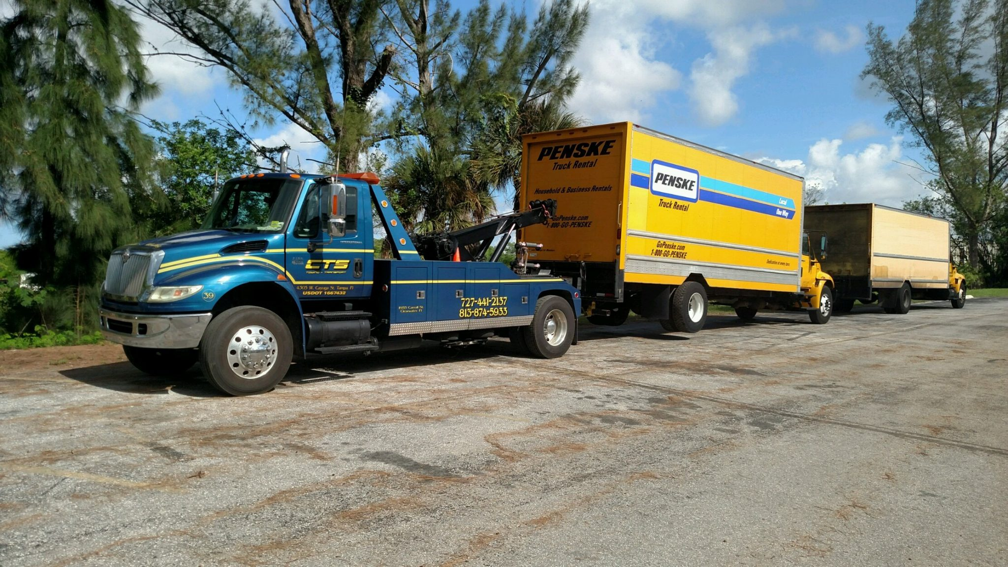 Medium duty penske box truck being towed by CTS Tow truck